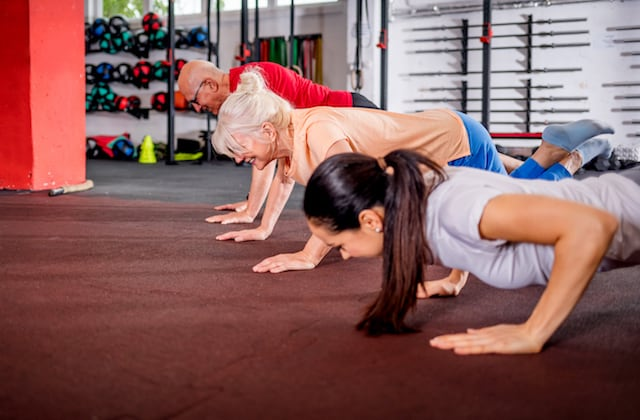 Senior people workout with personal trainer at the gym